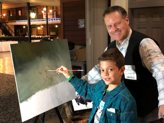 Jack Zabel helps artist Joe Kroneberg with his painting