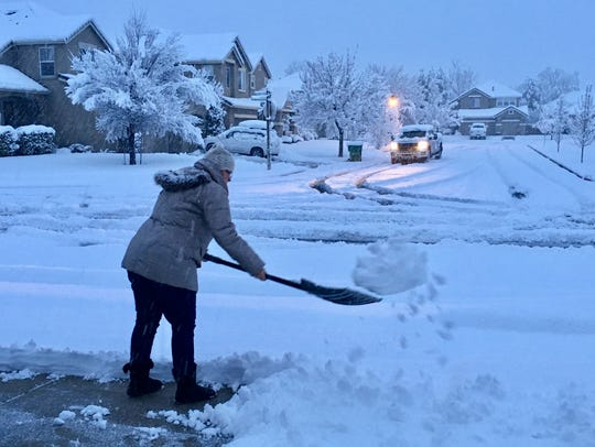 A woman shovels snow off her driveway in Reno on March
