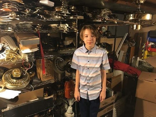 Reece Umbreit stands in the basement of his parent's home in North Fond du Lac, where he stores much of his fan collection.