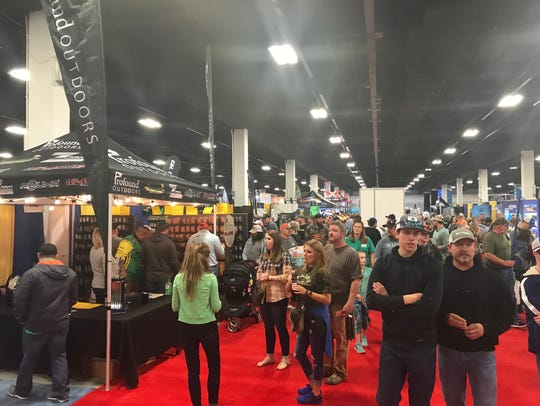 Visitors view exhibits at the Bassmasters expo Saturday.