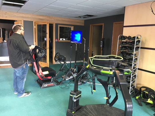 Edge VR Arcade co-owner Sean Bowers loads a racing