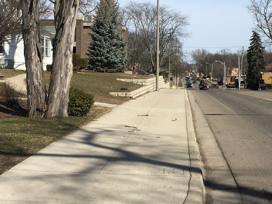 This photos shows the new sidewalk and retaining wall along Abbot Road.