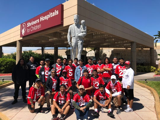The Immokalee boys lacrosse team poses outside of Shriners Hospital for Children in Tampa during the final day of its annual spring break trip. The Indians helped make repairs to playground equipment on the campus of the hospital.