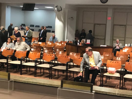 The podium at City Hall is moved behind a row of chairs