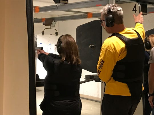 A Citizens Academy student shoots a gun in the gun range at the Manitowoc County Jail under the watchful eye of Manitowoc Police Captain Jason Freiboth March 20.