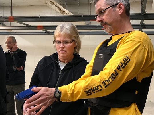 Manitowoc Police Captain Jason Freiboth shows Sally Rettinger how to hold a gun during the Citizens Academy class March 20.