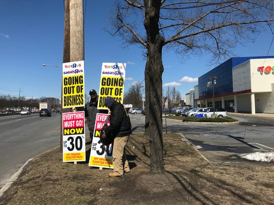 Highway sign walkers took their positions Friday to promote the liquidation sale at the Toys R Us on Route 17 in Paramus.