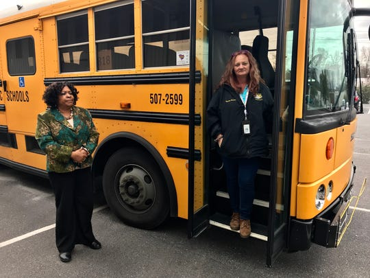 Greenville County school bus drivers Brenda Copeland, left, and Tammy Cummings pose in front of a bus after recalling their accidents last week.