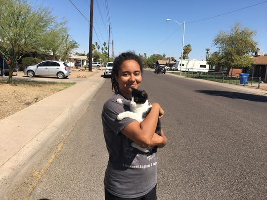 Ash Morgan holds Gypsy the cat on March 26, 2018, in Phoenix, after the feline was pulled down from a power pole, where at least one neighbor said the cat had been since Friday.
