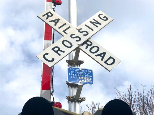 An emergency contact number at the railroad crossing