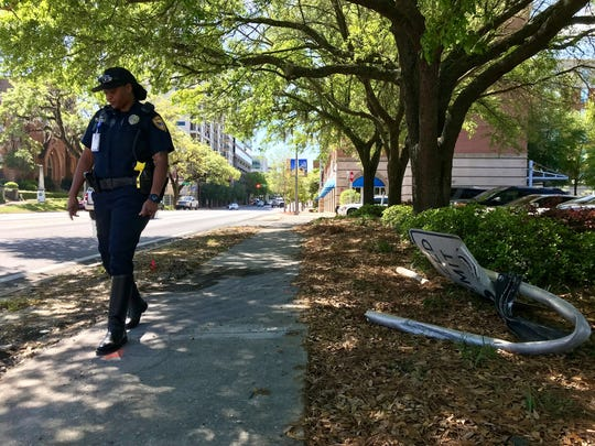 A Tallahassee police officer walks the scene of a fatal