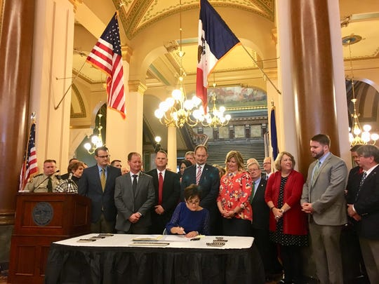 Gov. Kim Reynolds signs a bill Thursday, March 29,