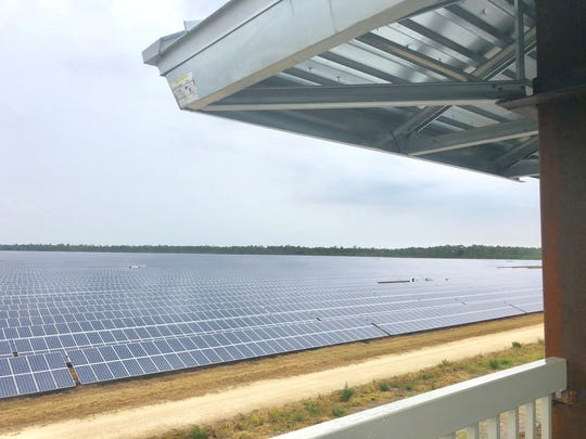Atop the platform, an ocean of solar panels fans out almost as far as the eye can see – save for a tree line off in the distance.