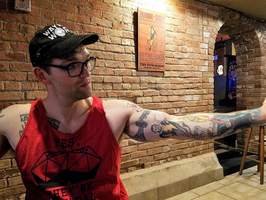 High Score Saloon co-owner Clint Hoskins has devoted one arm to super heroes, the other to super villains, and both to carrying vintage arcade games down two flights of stairs.