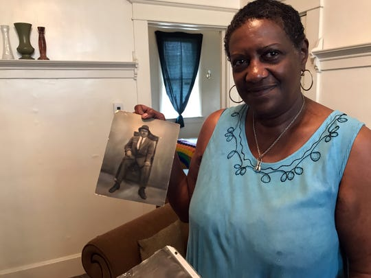 Alrita Pollard Lewis holds a picture of grandfather Lent Shaw inside her home in June 2017 in Evansville, Ind.