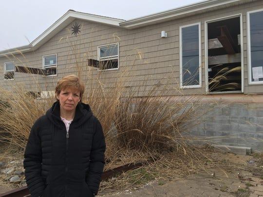 Lisa Lewis in front of her uninhabitable Waretown home.