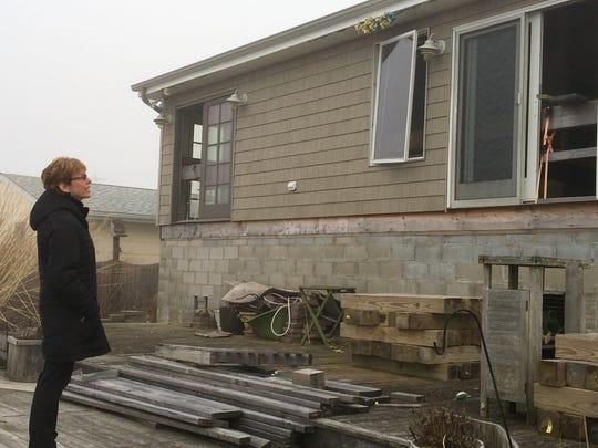 Lisa Lewis in back of her uninhabitable Waretown home.