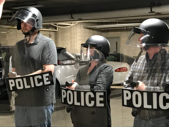 Citizens Academy students hold shields while they learn about crowd control at the Manitowoc Police Department.