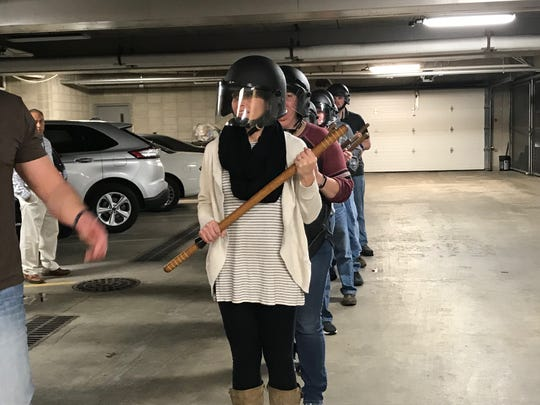 Citizens Academy students practice holding batons in a crowd control formation Tuesday.