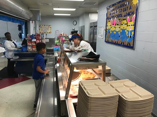 A cafeteria employee at North Salisbury Elementary School serves a student on April 4, 2018.