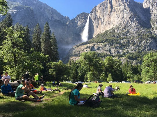 In this May 25, 2017 file photo, a class of eighth grade students and their chaperones sit in a meadow at Yosemite National Park below Yosemite Falls.