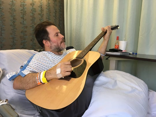 Ryan Payne in his rehabilitation bed, playing the guitar