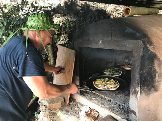 Felix Manglona bakes pizza in the hotnu (traditional Chamoru oven) at the third annual Valley of the Latte River Festival on April 8, 2018.