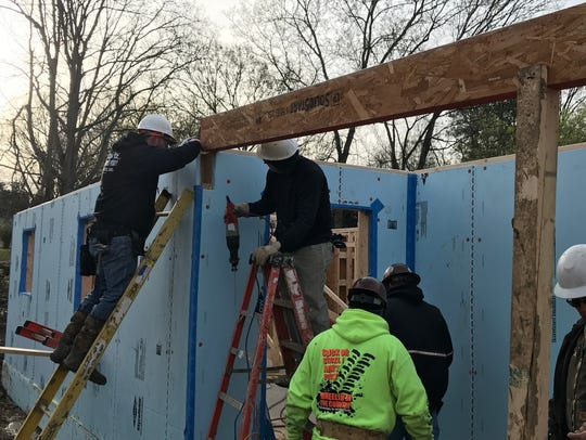 Volunteers from United Structural Systems work to build