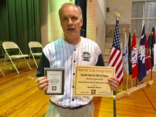 Michael Miller, a member of the board of directors of the Shoeless Joe Jackson Museum, holds a plaque and certificate naming Jackson to the Textile Sports Hall of Fame.