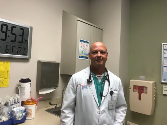 Dr. Hunter Brown, an emergency medicine physician, stands near a larger clock featured in all 18 private rooms in the emergency department at Physicians Regional Medical Center - Collier Boulevard. All 18 rooms in the ER are geriatric-friendly.