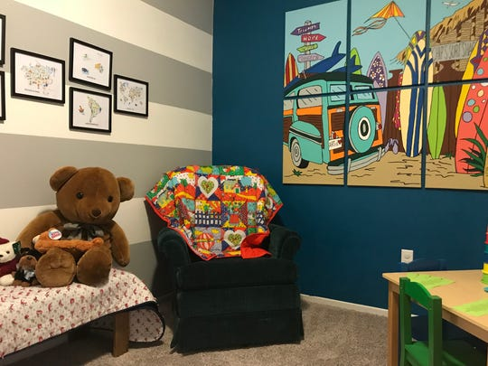 A bear and kid-size furniture sit in a playroom in