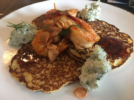 Johnny cakes come topped with shrimp, garlic, Calabrian chile sauce and creme fraiche at Catherine and Mary's.