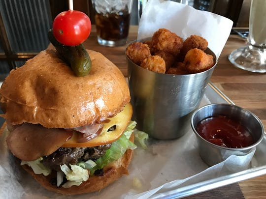 The Bushwood burger topped with bourbon apples, Prosciutto and smoked gouda and a side of Tots is on the menu at the new Farmer & The Cow restaurant in downtown Wilmington.
