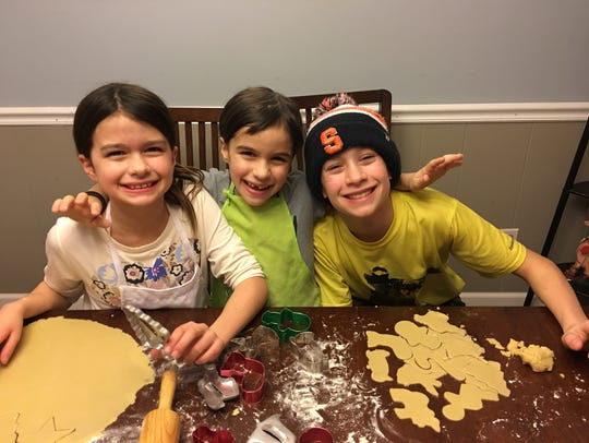 From left, Ella, Lucy and Tyler Buss make cookies.