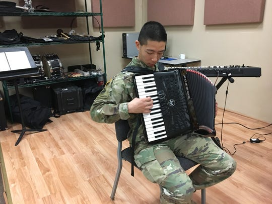 Spc. Pakkit Li plays the accordion as the 1st Armored
