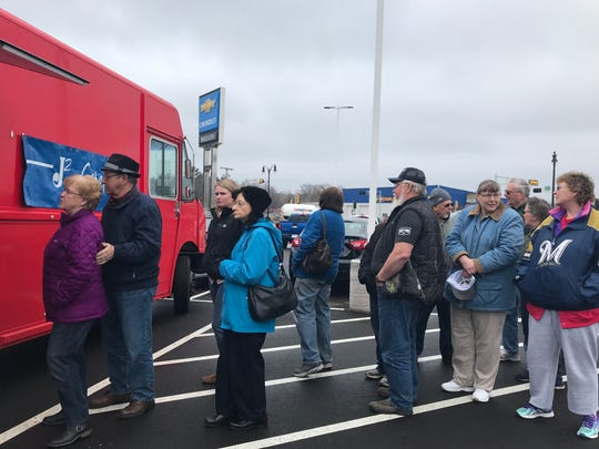 People stand in line for food at Wheelers Chevrolet's grand opening celebration April 12 in Wisconsin Rapids.