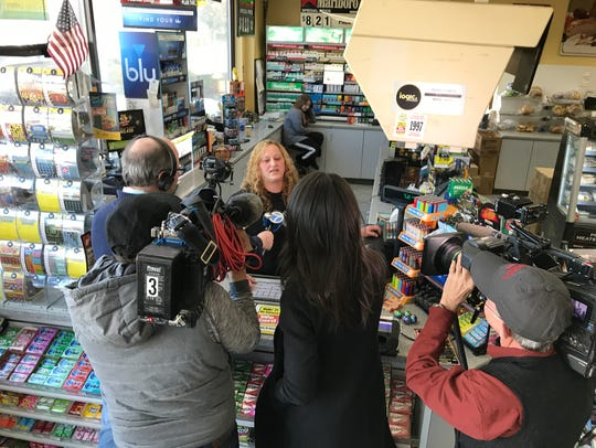 An attendant speaks to reporters after the NJ Lottery