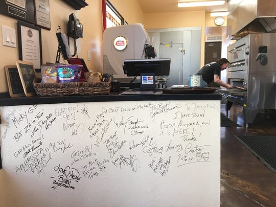 Autographs by musicians in bands such as Ambrosia, Toto and Stone Temple Pilots are seen on a wall between the kitchen and the dining room at Parma Pizzeria Napoletana in Thousand Oaks. The restaurant is owned by Mick Mahan, the longtime bassist for Pat Benatar and a trained pizzaiolo, or pizza maker.