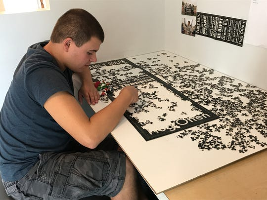 Luke Mulroony puts a puzzle together in his home in Totowa. Luke, 17, has autism and assembles puzzles as a hobby for others.
