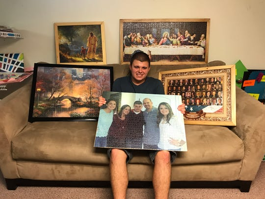 "Luke Mulroony displays several of the puzzles he has assembled. Many of the puzzles he's completed are framed on the wall in the basement of his house. Others are on display at the Totowa Public Library in April 2018 as part of the exhibit, ""Puzzled by Luke."""