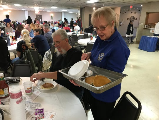 Randy Hasselbach, left, loads up on pancakes and sausage