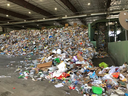 A mountain of trash to be recycled sits in the Waste Management transfer center. About 3.5 tons of the material collected each day cannot actually be recycled.