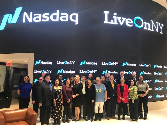 Denise Ely and other representatives from LiveOnNY gather to ring the NASDAQ closing bell April 2.