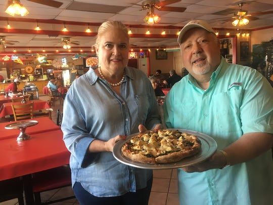 "Rita Hajjar and Fawaz ""Fuzzy"" Hajjar, owners of Fuzzy's Pizza & Cafe in Houston, show off their ""First Lady Barbara Bush's Pizza,"" a mix of chicken breast, spinach and artichoke favored by the former First Lady. Bush and husband, former president George H.W. Bush, were regulars at the pizzeria for more than 25 years."