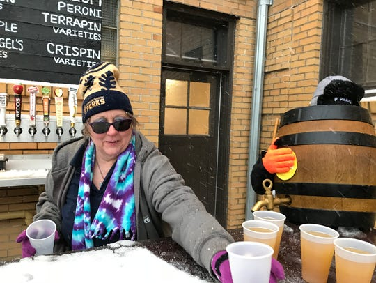 Leslie Weber serves a free beer at the South Shore Terrace's opening in 2018. More than 100 people braved wintry weather to attend the event.