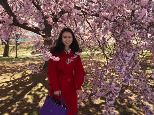 Jill Yang, 28, of New York City, is surrounded by blossoms in Branch Brook Park in Belleville and Newark on Friday, April 20, 2018.