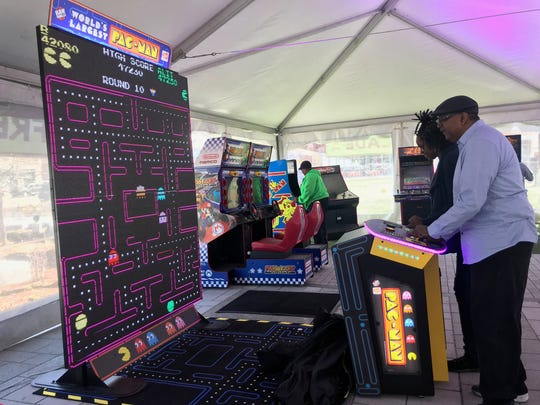 A free Parkcade in Beacon Park offers over 20 classic video games, each reinvented with 2018 technology. Detroiters Johnny Ballard, 58 (front) and Alita Page, 54, play PacMan on a big screen at the 'Power Up' at Beacon Park event on Friday, April 20, 2018.