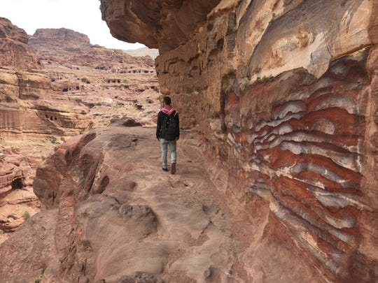 Ford Williams hikes down from the rock cave home of Mofleh Bdoul, a septuagenarian Bedouin.
