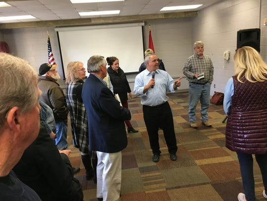 State Rep. Tim Wirgiau, center, fields questions about