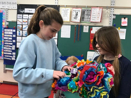 Aldo Leopold students Adah Danen and Briana Inda arrange paper flowers that will be delivered to Rebekah Haven, an assisted living facility.